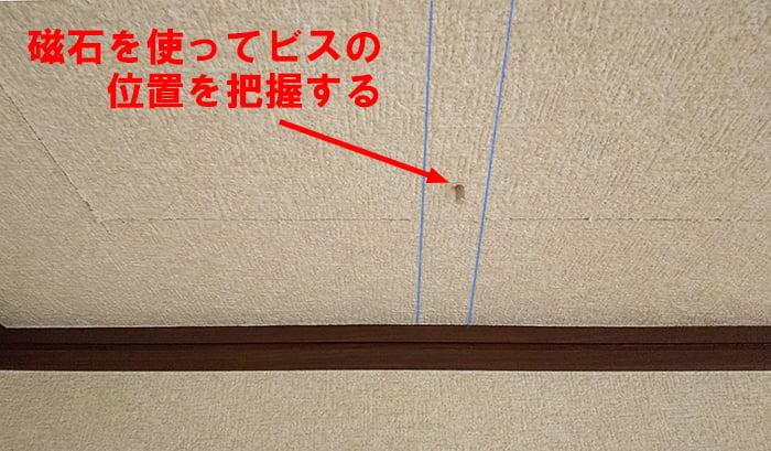 磁石を使ってビス位置を把握しようとしている写真画像 ※天井点検口の開け方(天井への点検口の作り方)解説画像3
