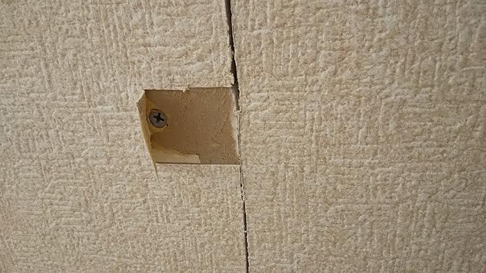 ビスのある箇所のクロスをめくった状態を撮影した写真画像 ※天井点検口の開け方(天井への点検口の作り方)解説画像4