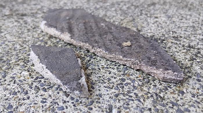 未だに落ちている隣地のスレート屋根の残骸を撮影した写真画像