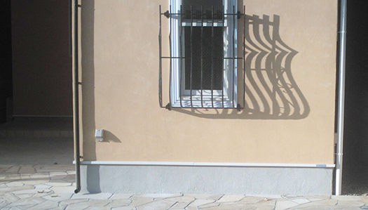 モルタル+吹付けの外壁を撮影した写真画像(腰窓の上下窓も写っている画像)