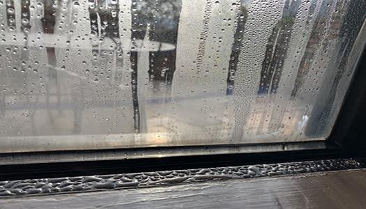 気温差と高湿度によって腰窓に生じている結露を撮影した写真画像