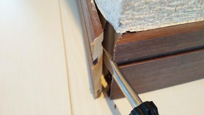 巾木コーナーキャップ破損部の巾木を開いている近景を撮影した写真画像 ※巾木コーナーキャップ形状解説のため部材を取り出そうとしている写真1