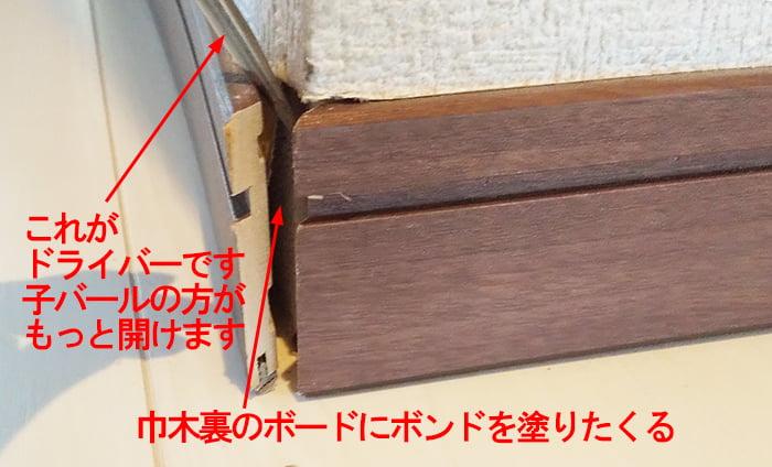 裏側にボンドを仕込むために巾木を少し開いている様子を撮影したコメント入り写真画像 (巾木コーナーキャップ補修解説写真2)
