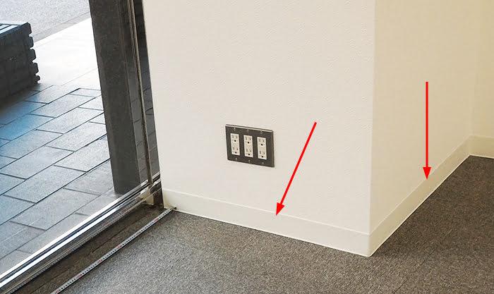 とあるテナントのタイルカーペット床に対し貼られたソフト巾木を撮影した写真に解説用矢印を入れた写真画像①