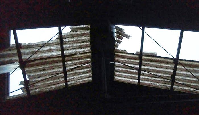 挿絵:とある建物の剥がれた屋根の見上げを撮影した写真画像 (火災保険でのリフォームや修繕ができる例)