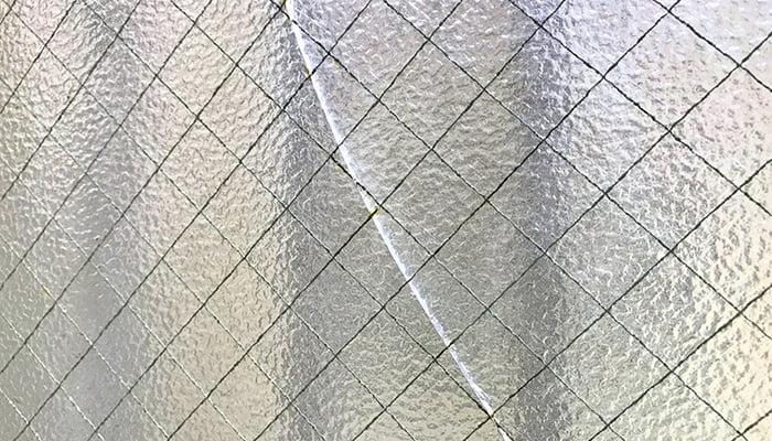 挿絵:網入りガラスのひび割れを撮影した写真画像 (火災保険でのリフォームや修繕が微妙な例)