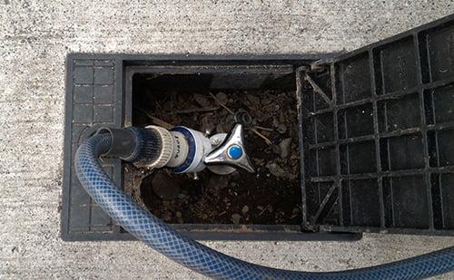 改善前の建売マイホームの散水栓の蓋を開けた状態(ホースはつけっぱなし)の写真画像