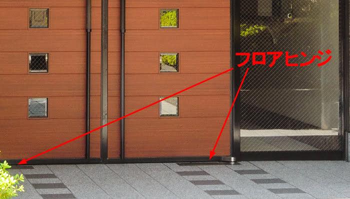 とあるマンションのエントランスドアに使われた持出し吊り型FH(フロアヒンジ)を撮影したコメント入り写真画像
