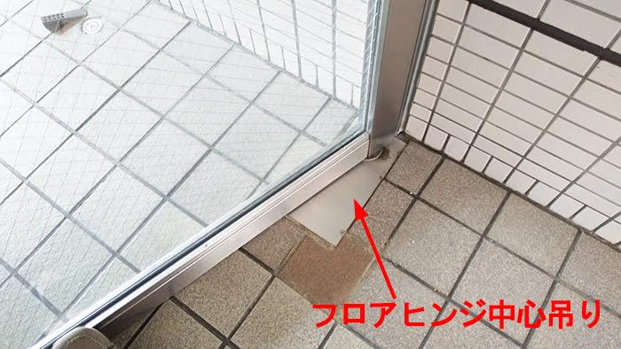 とあるアパートのエントランスドアに使われた中心吊り型FH(フロアヒンジ)を撮影したコメント入り写真画像