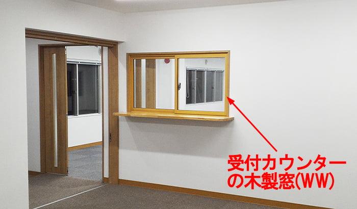 とあるオフィスの受付カウンターに設置された木製窓(略語WWの例)を撮影したコメント入り写真画像