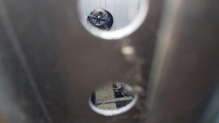 筆者の建売マイホームのキュルキュルの音鳴りが酷い和室サッシ内障子の反対側の縦框の組立用ネジ穴から覗いた調整ネジの頭を撮影した写真画像