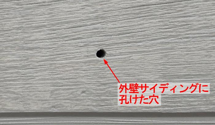 傘掛け設置のためにサイディング外壁に孔けた穴を撮影したコメント入り写真画像
