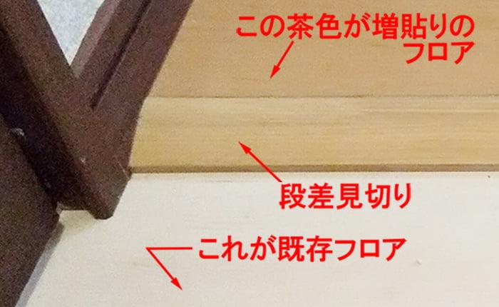 フローリングの重ね張りによって生じる段差処理例として段差見切り設置部分を撮影した解説コメント入り写真画像