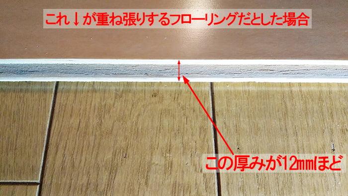 フローリングの重ね張りイメージ02ということで、元のフローリングの上に新たなフローリングを載せて撮影した解説コメント入り写真画像