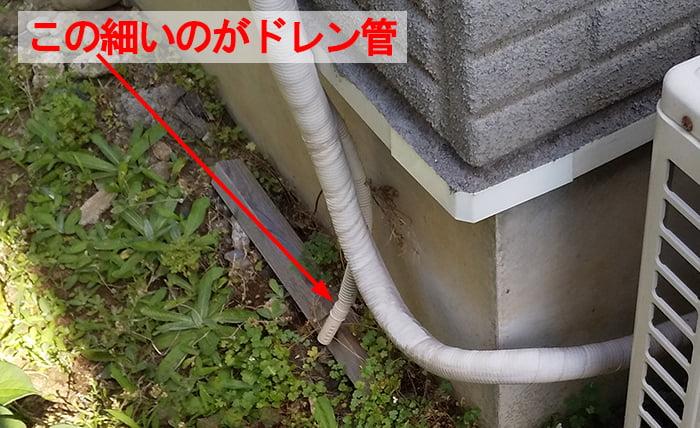 エアコン冷媒配管とは別に落とされているドレン管を撮影したコメント入り写真画像