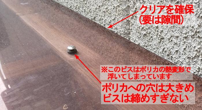 ポリカを割れないように施工するポイント3:ポリカへの穴孔けは大きめにして緩めに固定した勝手口屋根のポリカーボネート(ポリカ)板を拡大撮影したコメント入り写真画像