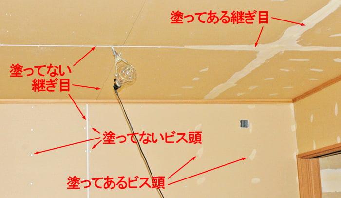 ボード継ぎ目とビス頭が写ったパテ施工中の様子を撮影したコメント入り写真画像